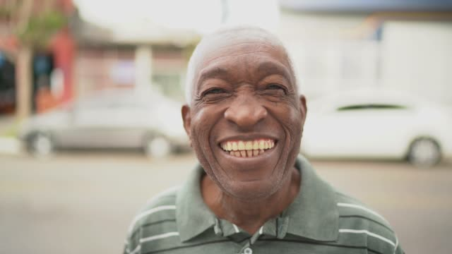 vídeos de stock, filmes e b-roll de retrato do homem afro de sorriso que olha a câmera na rua - simplicidade