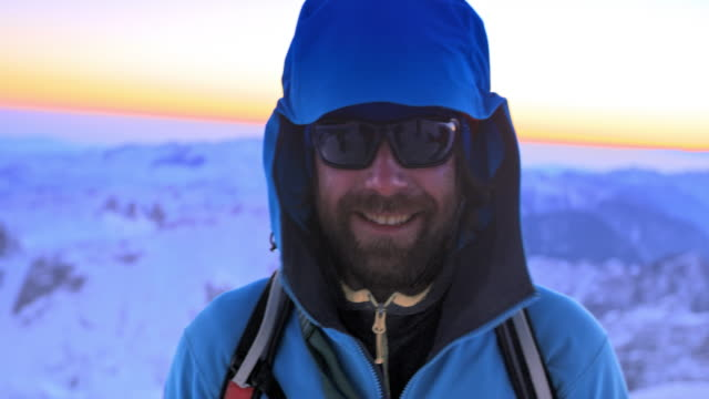 PAN Portrait of smiling alpinist on snowy mountain top at sunset