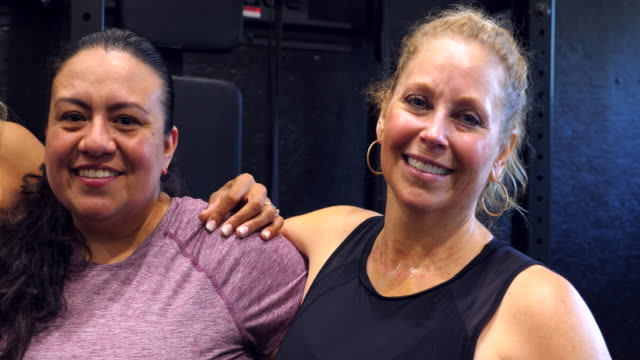 vídeos de stock, filmes e b-roll de pan portrait of smiling and laughing womens fitness class after workout in gym - 40 49 anos