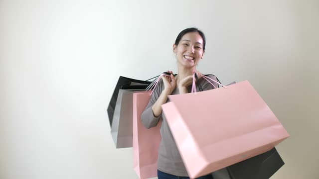 portrait of smiling asian beautiful woman carrying shopping bags in hand - shopping bag stock videos & royalty-free footage