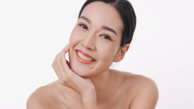 portrait of smiling asian woman applying face cream with white background. - beautiful people stock videos & royalty-free footage