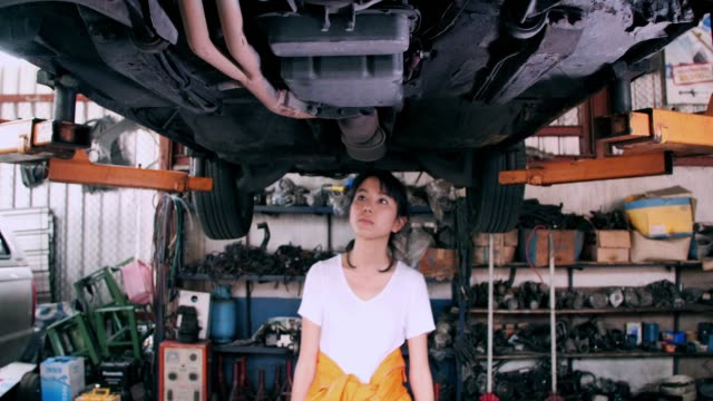 portrait of smiling asian young women craftswoman and dancing with her tools around her in her workshop - funky stock videos and b-roll footage