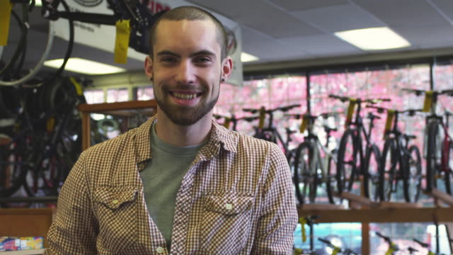 cu portrait of smiling bike shop employee / portland, oregon, usa - portland oregon bike stock videos & royalty-free footage