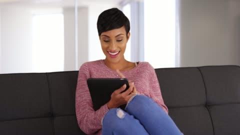 portrait of smiling black female sitting on sofa using tablet in living room - endast unga kvinnor bildbanksvideor och videomaterial från bakom kulisserna
