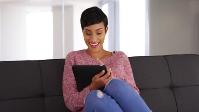 vídeos y material grabado en eventos de stock de portrait of smiling black female sitting on sofa using tablet in living room - sólo mujeres jóvenes