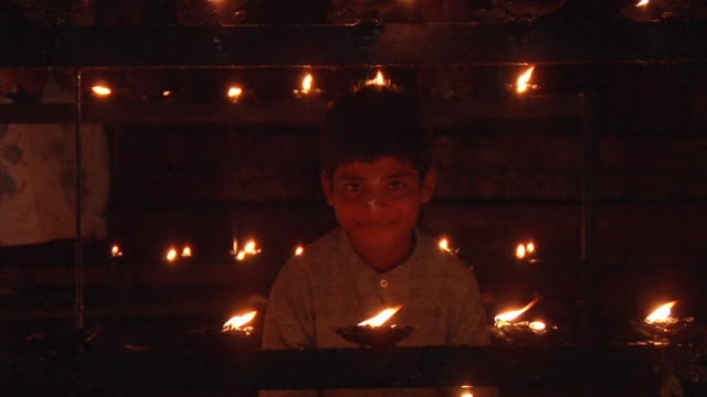CU, Portrait of smiling boy (8-9) standing behind lit oil lamps, Hampi, Karnataka, India