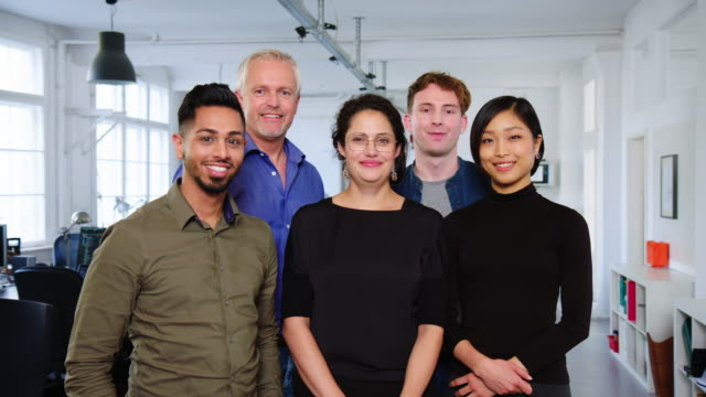 portrait of smiling business team standing together in office - creative occupation stock videos & royalty-free footage
