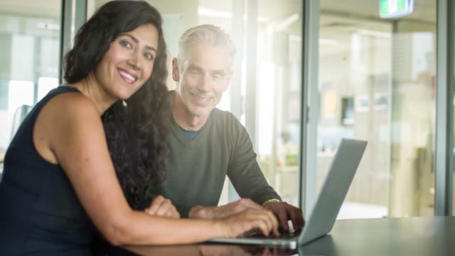 Portrait of smiling businessman and businesswoman using laptop in office