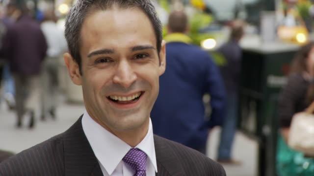 CU Portrait of smiling businessman on busy street / New York City, New York, USA