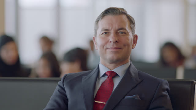 slo mo. portrait of smiling businessman seated in airport terminal waiting area. - finanzwirtschaft und industrie stock-videos und b-roll-filmmaterial