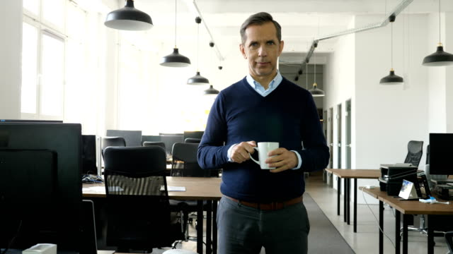portrait of smiling businessman with mug at office - pendant light stock videos & royalty-free footage