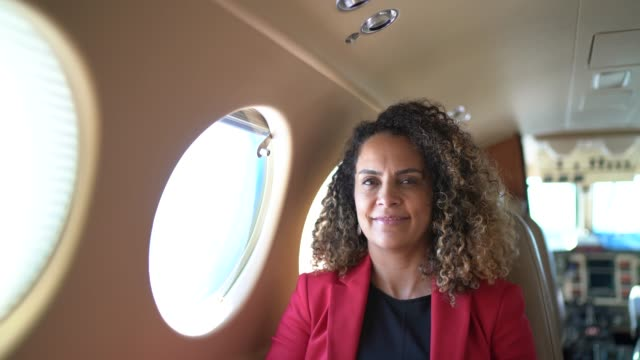 portrait of smiling businesswoman looking at camera in a corporate jet - profile view stock videos & royalty-free footage