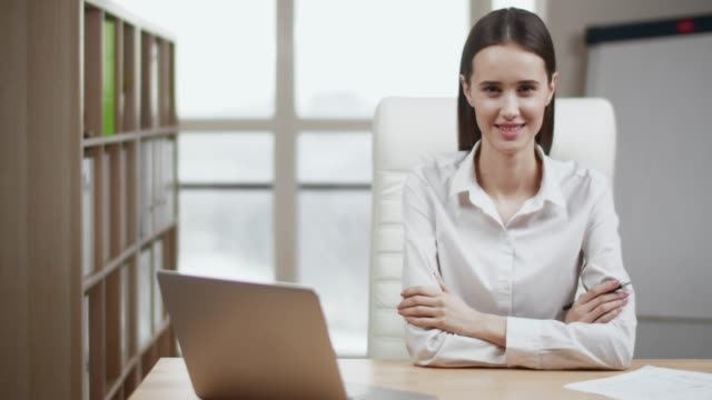 stockvideo's en b-roll-footage met portret van glimlachende zakenvrouw kijken naar camera poseren - looking at camera
