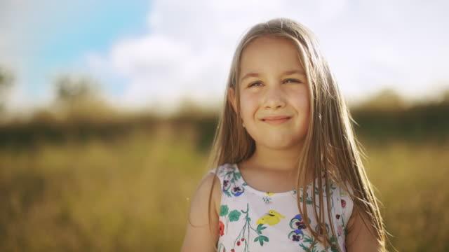 自然の中でカメラを見て笑顔の白人の小さな女の子の肖像画 - 少女点の映像素材/bロール