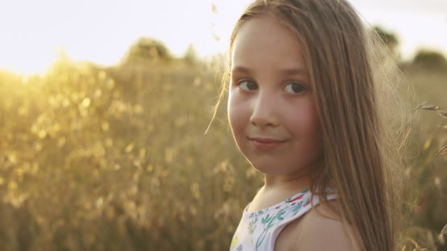 portrait of smiling caucasian little girl looking at the camera in nature - grass family stock videos & royalty-free footage