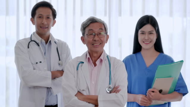 portrait of smiling confident team of doctors, nurses and assistants.professional medical personnel working.diverse team of medical scientist posing with crossed arms in the hospital and looking at camera in medical office.medical concept - physical therapist stock videos & royalty-free footage
