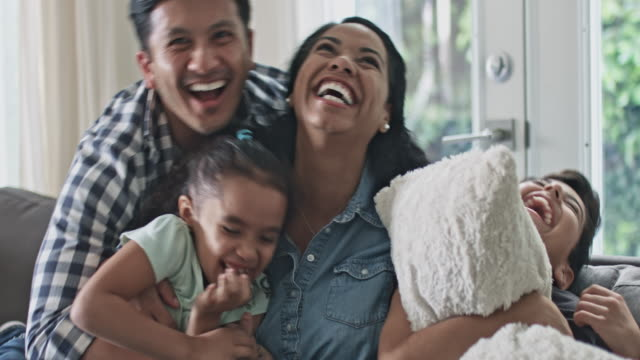 portrait of smiling family having fun tickling in sofa at home - etnia latino americana video stock e b–roll