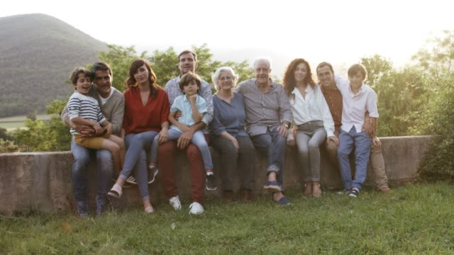 portrait of smiling family sitting in yard - family stock videos & royalty-free footage