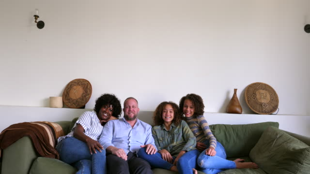 ws td portrait of smiling family sitting together on couch in living room - living room stock videos & royalty-free footage