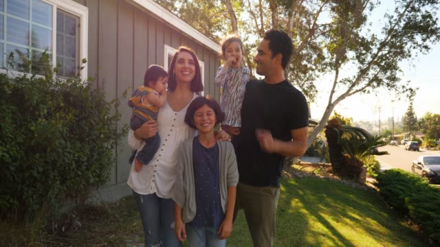ms portrait of smiling family standing in front yard of home - family with three children stock videos & royalty-free footage