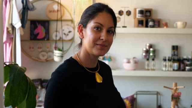 vidéos et rushes de cu portrait of smiling female business owner standing in boutique - latino américain