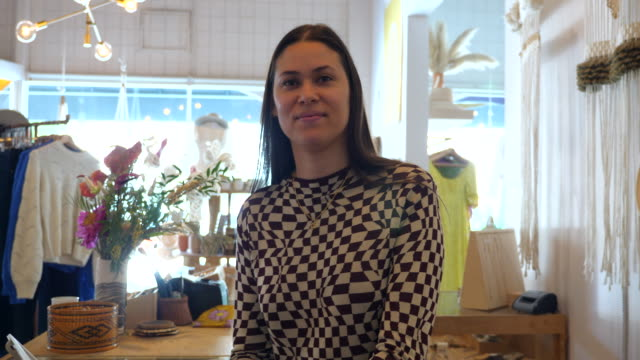 ms portrait of smiling female clothing boutique owner standing in store - owner stock videos & royalty-free footage