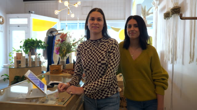 ms portrait of smiling female clothing boutique owners standing at counter in store - clothes shop stock videos & royalty-free footage