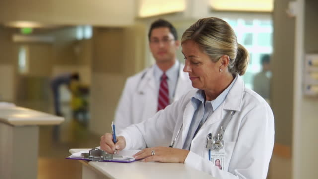 stockvideo's en b-roll-footage met ms portrait of smiling female doctor filling out patient's chart in hospital, seattle, washington, usa - medische status