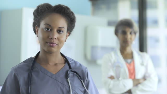 portrait of smiling female doctor with colleague standing in background - st. louis missouri stock videos & royalty-free footage