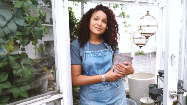 portrait of smiling female greenhouse owner with flower pots leaning at doorway - plant pot stock videos & royalty-free footage