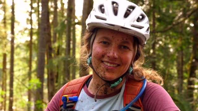 cu portrait of smiling female mountain biker after muddy bike ride - 強靭性点の映像素材/bロール