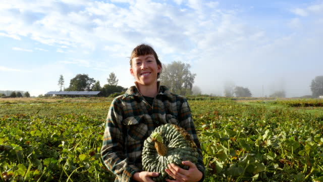 MS Portrait of smiling female organic farmer picking up squash in field on fall morning