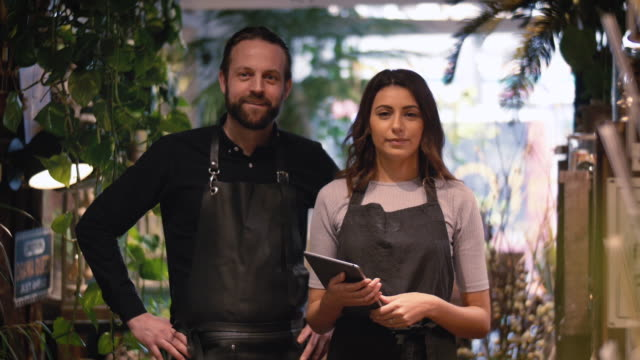portrait of smiling female owner holding digital tablet while standing by male coworker in flower shop - fioraio negozio video stock e b–roll