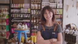 Portrait Of Smiling Female Owner Standing Arms Crossed In Delicatessen