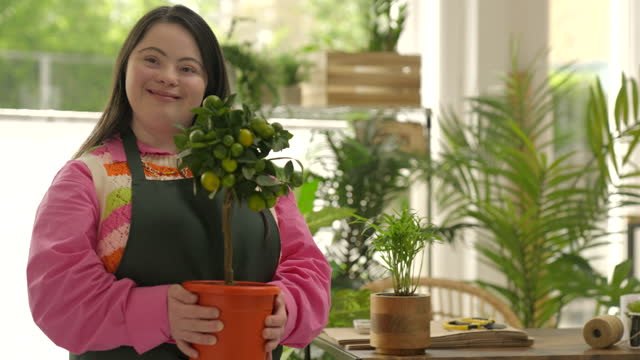 portrait of smiling florist holding plant in flower shop - disability stock videos & royalty-free footage