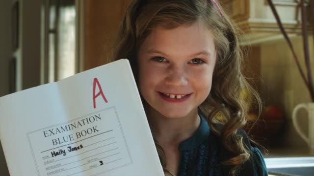 vídeos de stock e filmes b-roll de cu tu portrait of smiling girl (8-9) holding test with a grade / cedar hills, utah, usa - resultado de exame