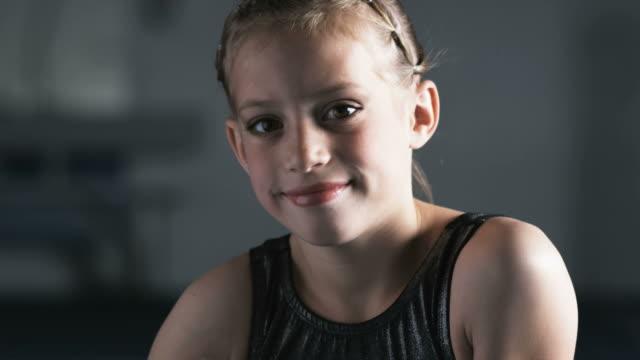 cu portrait of smiling girl (8-9) in gym, orem, utah, usa - leotard stock videos and b-roll footage