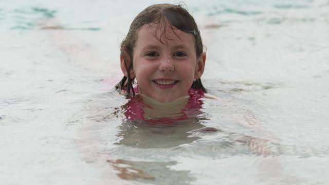 slo mo ms portrait of smiling girl (6-7) in swimming pool / cedar hills, utah, usa - piscina pubblica all'aperto video stock e b–roll