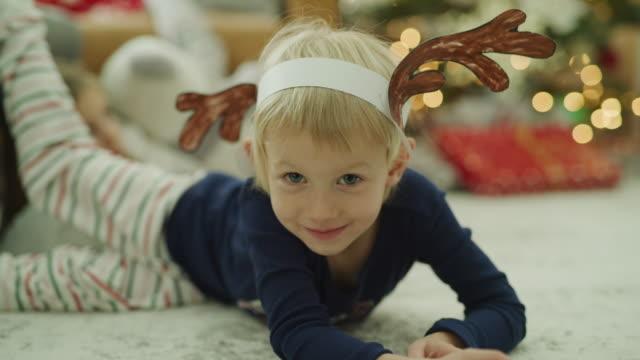Portrait of smiling girl laying on floor wearing paper antlers on Christmas / Vineyard, Utah, United States