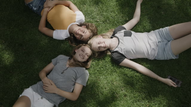 vidéos et rushes de portrait of smiling girls laying head to head on grass / provo, utah, united states - être étendu