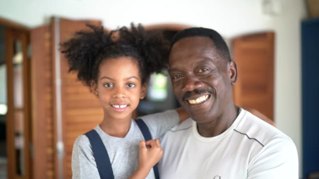portrait of smiling grandfather and granddaughter at home - 50 54 years stock videos & royalty-free footage