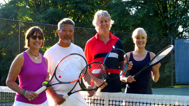 ms portrait of smiling group of senior friends standing on tennis court before early morning match - courtyard stock videos & royalty-free footage
