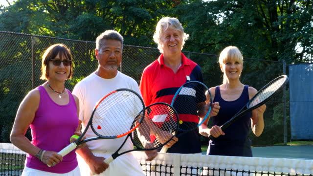 ms portrait of smiling group of senior friends standing on tennis court before early morning match - gårdsplan bildbanksvideor och videomaterial från bakom kulisserna