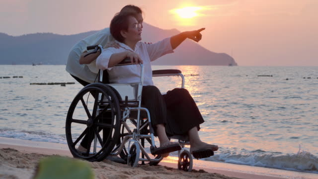 portrait of smiling happy asian senior mother with her adult daughter hugging on the beach.happy daughter is holding caregiver for a hand while spending time together.senior holidays,vacations,care,retirement,family concept,traveling with differing abilit - disability support stock videos & royalty-free footage