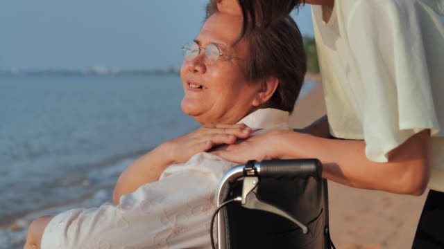 portrait of smiling happy asian senior mother with her adult daughter hugging on the beach.happy daughter is holding caregiver for a hand while spending time together.senior holidays,vacations,care,retirement,family concept,traveling with differing abilit - emotional support stock videos & royalty-free footage
