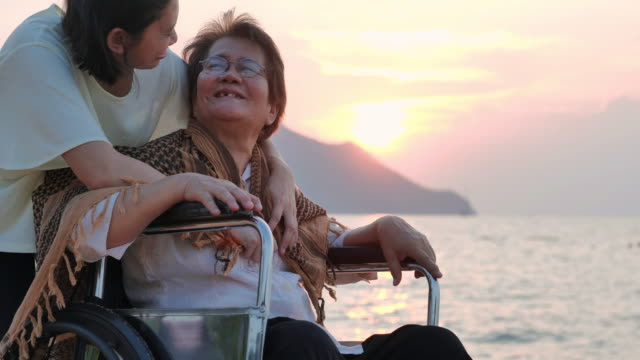 vídeos de stock e filmes b-roll de portrait of smiling happy asian senior mother with her adult daughter hugging with a blanket on the beach.senior holidays,vacations,care,retirement,family concept,traveling with differing abilities - cadeira de rodas