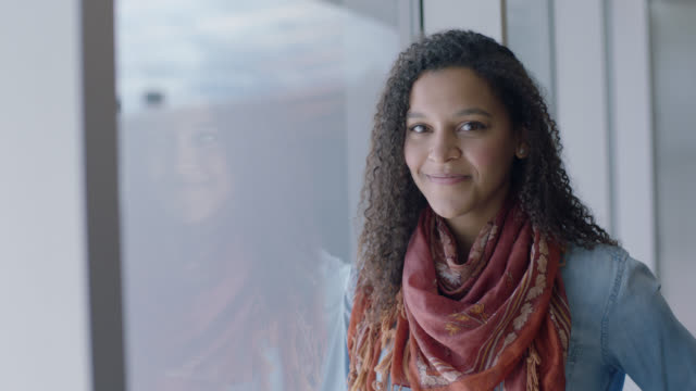 slo mo. portrait of smiling hip young mixed-race woman standing next to airport terminal window. - person in education stock videos and b-roll footage