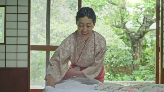 portrait of smiling landlady laying futon in hotel - japanese culture stock videos & royalty-free footage