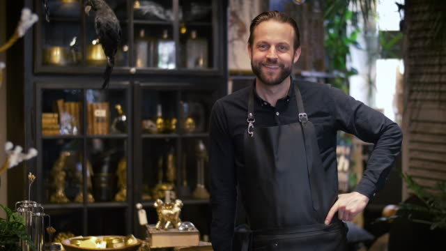 portrait of smiling male owner standing with hand on hip in flower shop - hand on hip stock videos & royalty-free footage