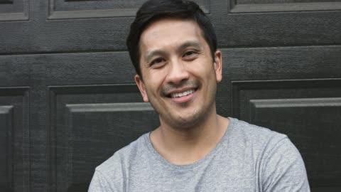 portrait of smiling man against garage door in backyard - t shirt stock videos & royalty-free footage